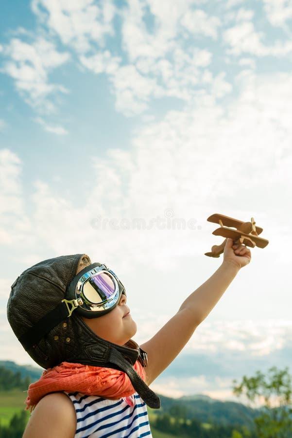 Счастливый ребенк играя с деревянным самолетом игрушки против голубого лета s стоковое изображение rf