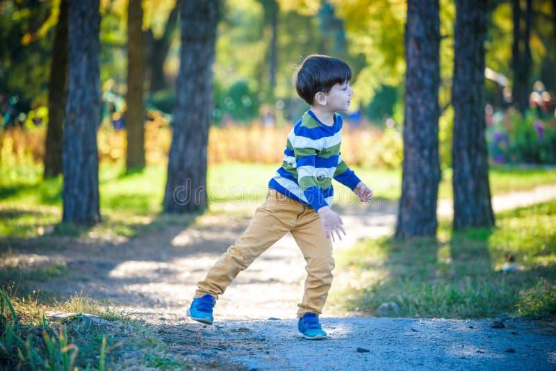 Счастливый ребенк играя с самолетом игрушки против голубой предпосылки неба лета Самолет пены хода мальчика в лесе или парке Само стоковая фотография rf
