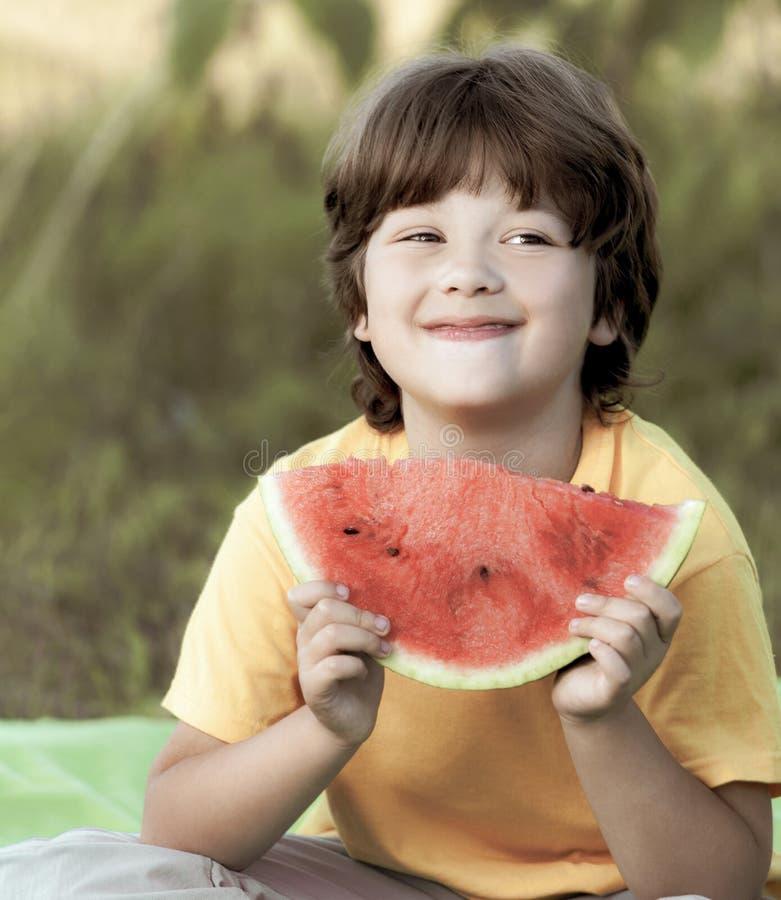 Счастливый ребенок есть арбуз в саде Мальчик с парком outdoors плода стоковые фотографии rf