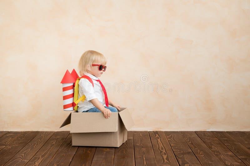 Счастливый ребенок играя с ракетой игрушки дома стоковые фото
