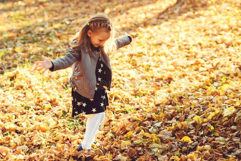 Счастливый ребенок идя в парк осени Ребенок бросая упаденные листья вверх Красивое золотое время осени Счастливый и здоровый ребе стоковое изображение rf