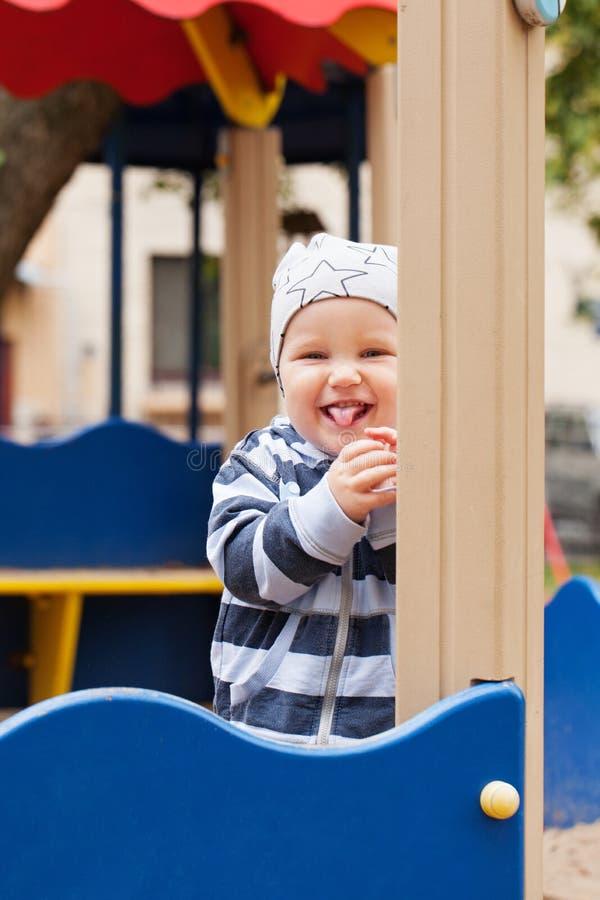 Счастливый ребенок имея потеху на спортивной площадке outdoors стоковые фотографии rf