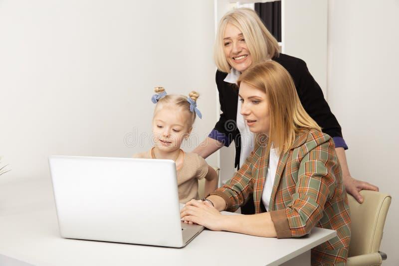 Счастливый ребенок с бабушкой и матерью используя ноутбук совместно стоковое фото rf