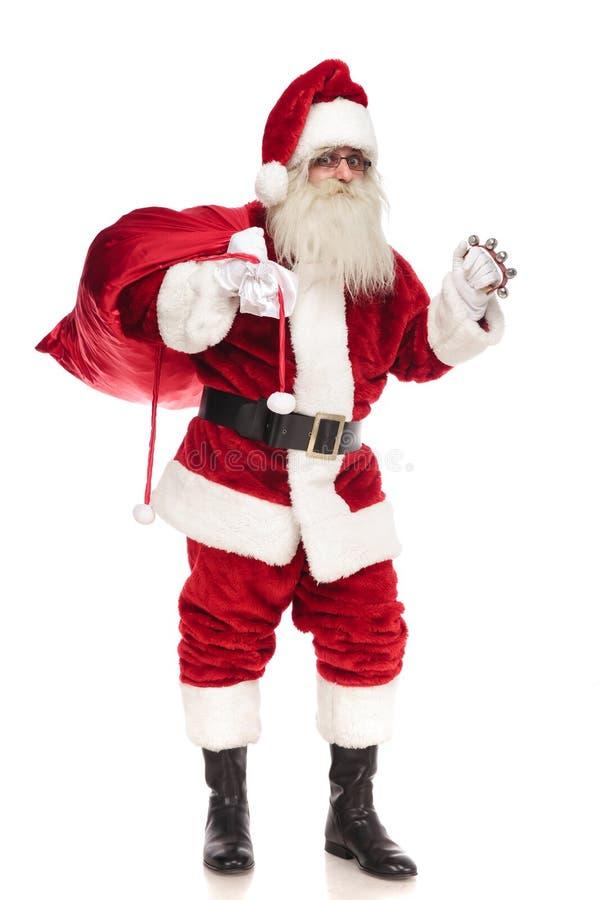 Счастливый Санта Клаус держа красную сумку и звеня его колокол стоковая фотография rf