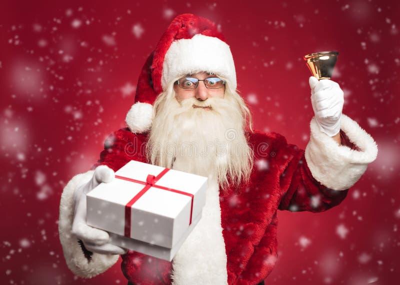 Счастливый Санта Клаус звеня его колокол и предлагая настоящий момент стоковое фото