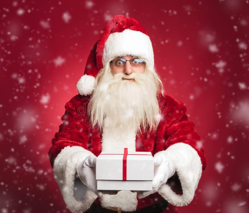 Счастливый Санта Клаус предлагая настоящий момент ко всем детям стоковое фото