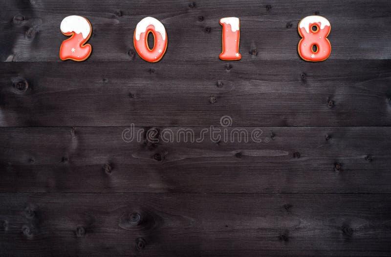Счастливый символ знака Нового Года 2018 от красных и белых печений пряника на темной деревянной предпосылке, космосе экземпляра  стоковые изображения rf