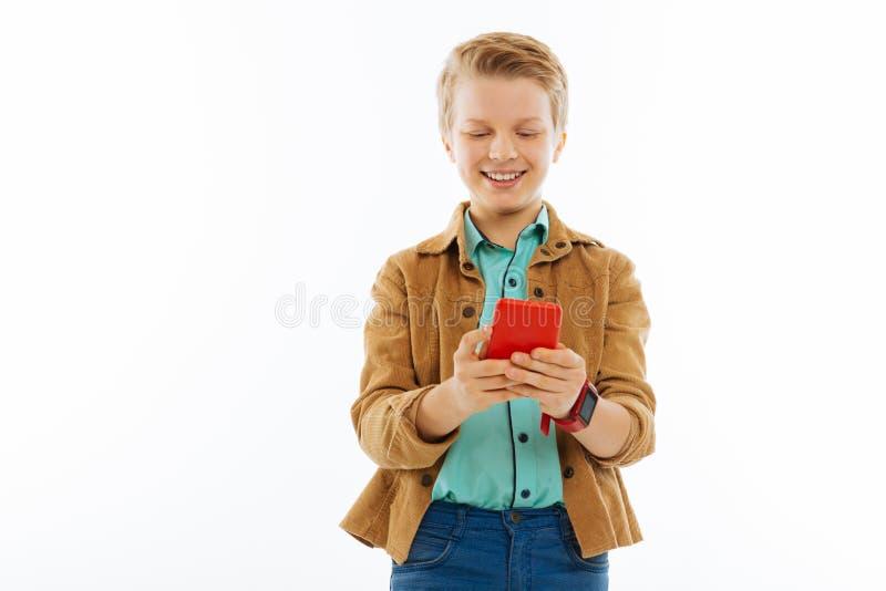 Счастливый славный мальчик печатая сообщение по его телефону стоковое изображение