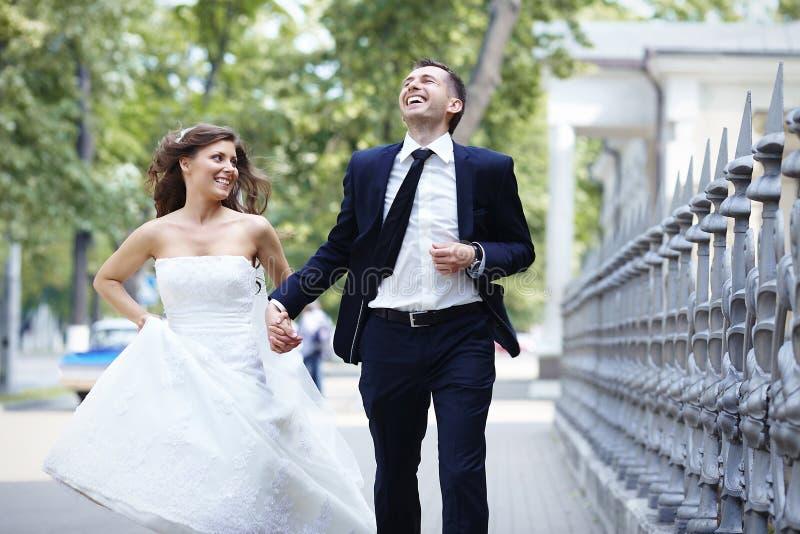 Счастливый смех хода жениха и невеста смеясь над на день свадьбы стоковая фотография