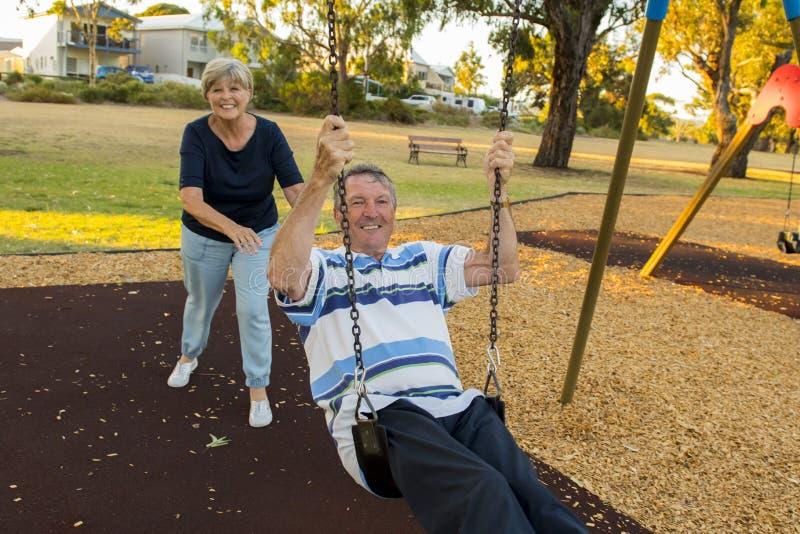 Счастливый старший американский наслаждаться пар около 70 лет старый на парке качания при жена нажимая супруга усмехаясь и имея п стоковые изображения rf