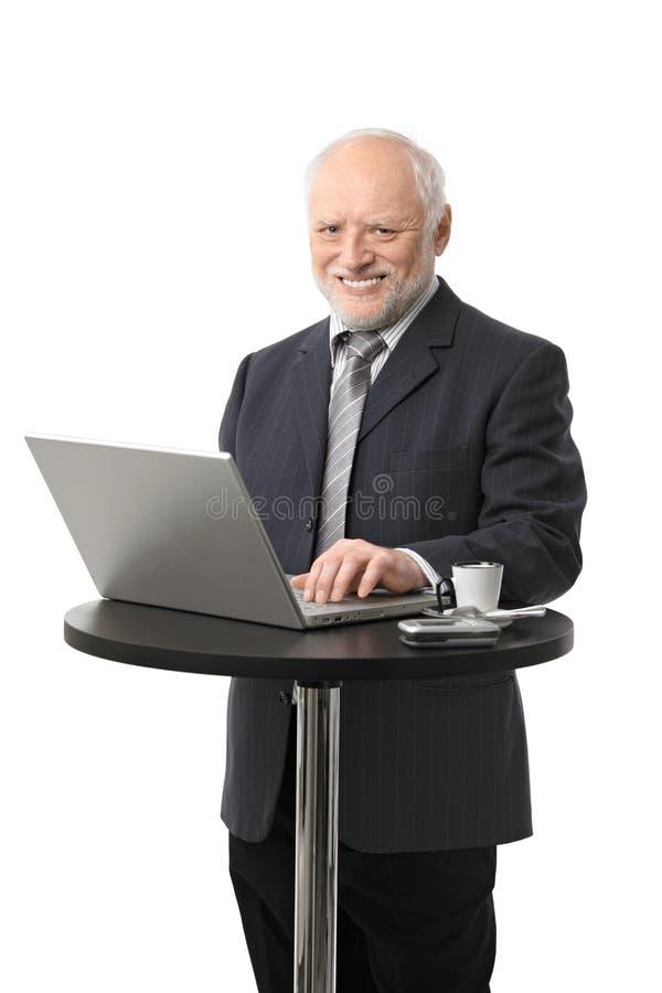 Счастливый старший бизнесмен используя компьютер стоковые фото