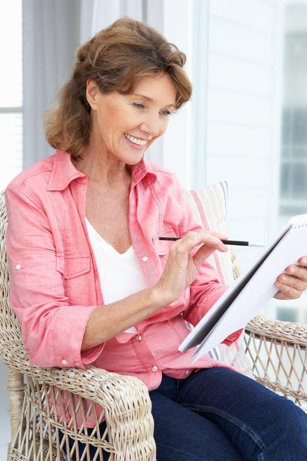 Счастливый старший делать эскиз к женщины стоковые изображения
