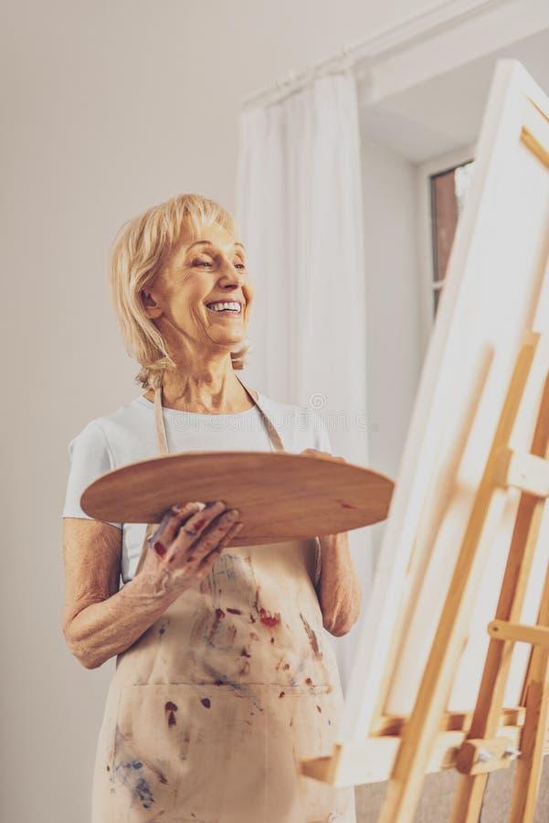 Счастливый старший женский человек смотря ее мольберт стоковые фото