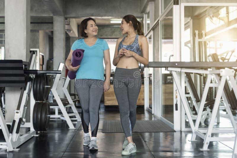 Счастливый старший и молодая женщина пар фитнеса держа циновки йоги стоковые фотографии rf