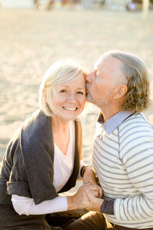 Счастливый старший супруг целуя пожилую жену и сидя на пляже песка стоковое изображение