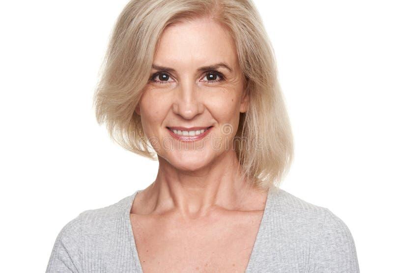 Счастливый старый белокурый усмехаться женщины изолировано стоковые изображения