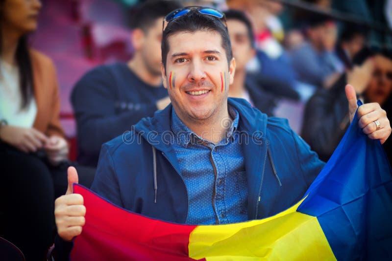Счастливый сторонник держа румынский национальный флаг в руках на человек международном †спортивного мероприятия «в стойках вес стоковая фотография rf