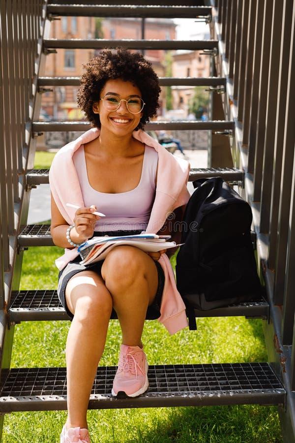 Счастливый студент сидя на лестнице стоковые изображения