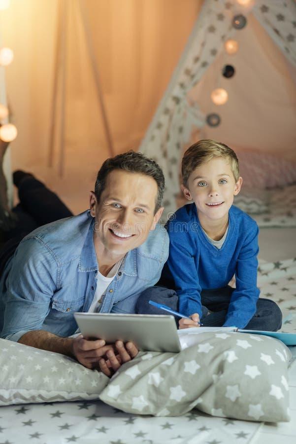 Счастливый сын и папа делая домашнюю задачу совместно стоковое изображение