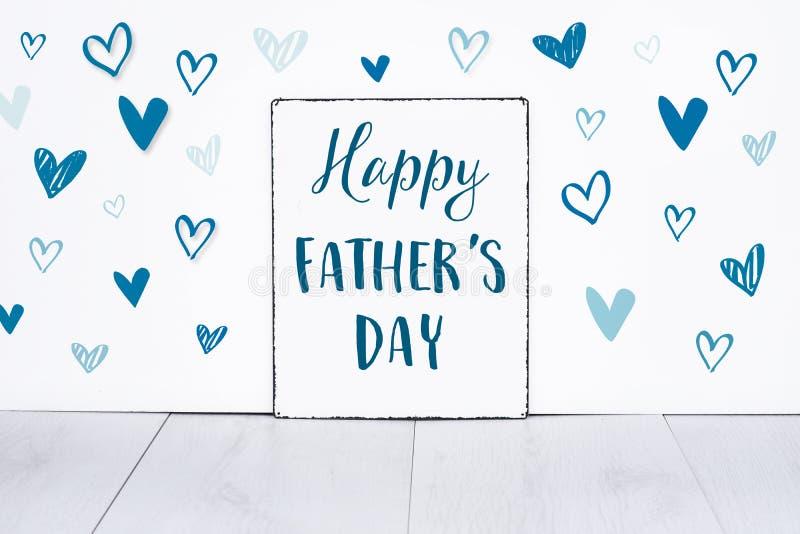 Счастливый текст дня отцов на доске знака для самого лучшего папы в мире с милыми маленькими голубыми сердцами на белой предпосыл стоковое изображение rf