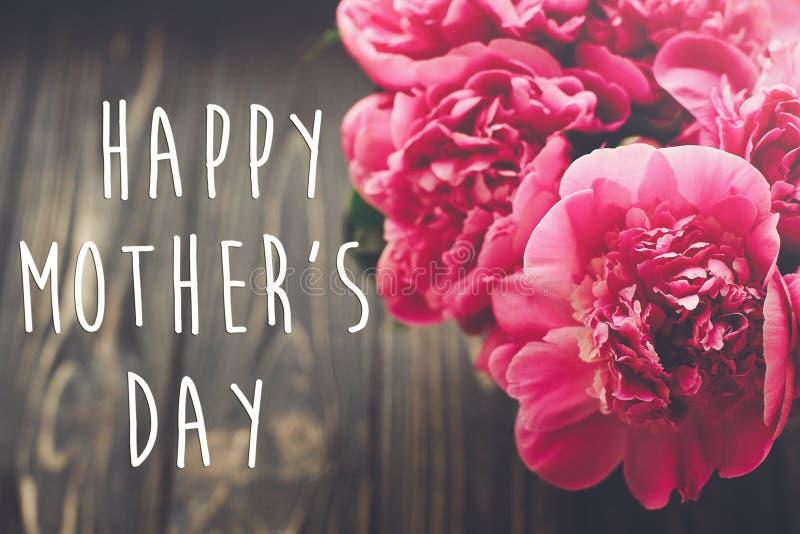 Счастливый текст дня ` s матери на розовом букете пионов на деревенской темноте w стоковые фото