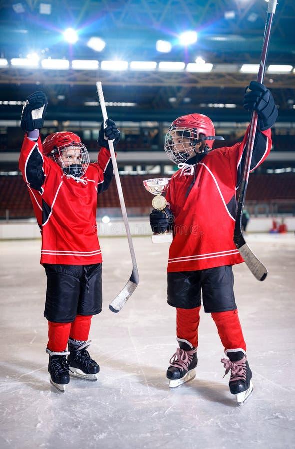 Счастливый трофей победителя хоккея на льде игроков мальчиков стоковые изображения