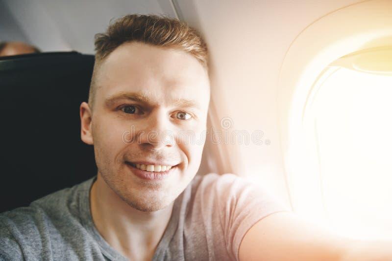 Счастливый туристский человек делает фото selfie в самолете воздушных судн кабины перед отклонением r стоковые изображения