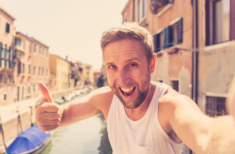 Счастливый туристский человек усмехаясь и показывая большой палец руки вверх пока принимающ selfie на канале в Венеции Италии стоковая фотография