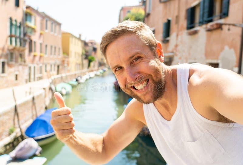 Счастливый туристский человек усмехаясь и показывая большой палец руки вверх пока принимающ selfie на канале в Венеции Италии стоковая фотография rf