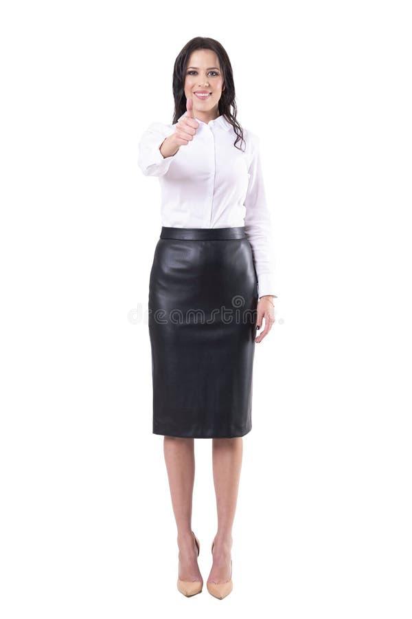 Счастливый удовлетворенный усмехаясь молодой взрослый большой палец руки показа бизнес-леди вверх на камере стоковое фото rf