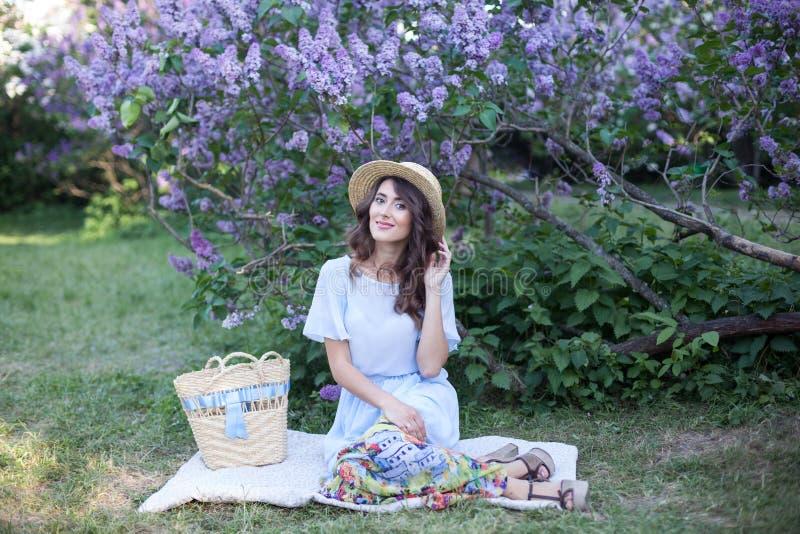 Счастливый уклад жизни женщины, портрет красивой девушки в соломенной шляпе сидя около цвести сирени в лучах заходящего солнца стоковые изображения