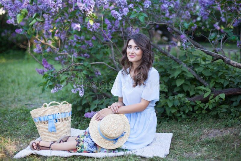Счастливый уклад жизни женщины, портрет красивой девушки в соломенной шляпе сидя около цвести сирени в лучах заходящего солнца стоковое фото rf