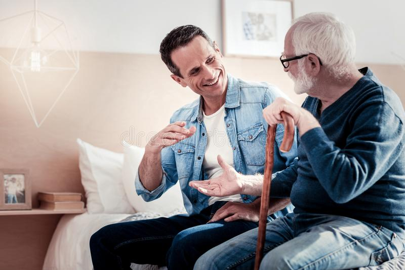 Счастливый услаженные отец и сын смотря фото стоковые изображения rf