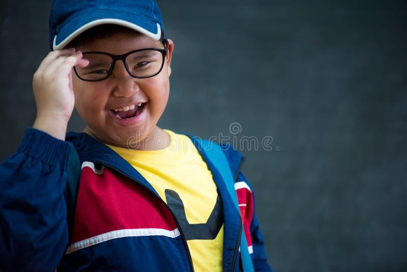 Счастливый усмехаясь азиатский мальчик в стеклах идет к schoo стоковое изображение