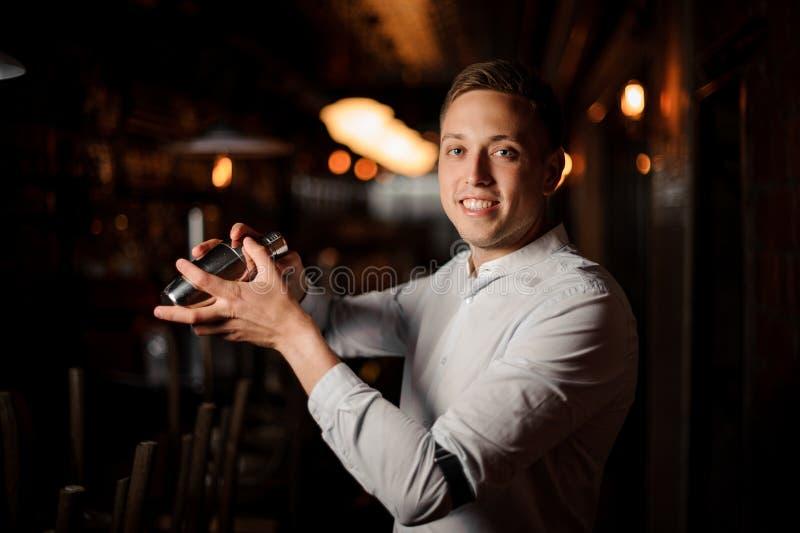 Счастливый усмехаясь бармен делая свежий коктеиль в шейкере стоковые фото