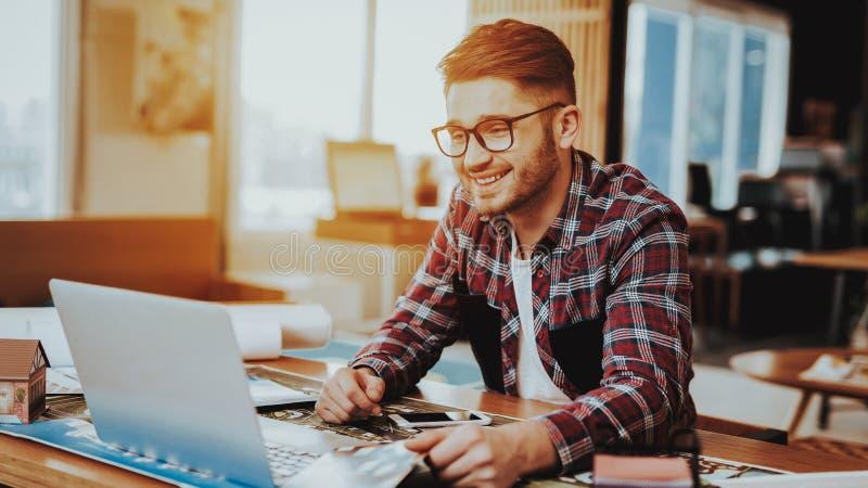 Счастливый усмехаясь иллюстратор сфокусированный на проекте работы стоковые изображения
