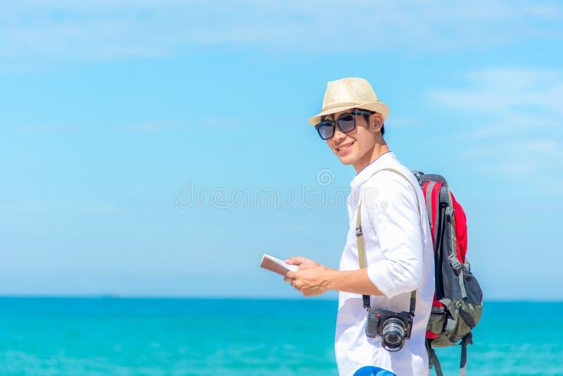 Счастливый усмехаясь кавказский туристский азиатский молодой человек смотря пасспорт с камерой на пляже стоковое фото