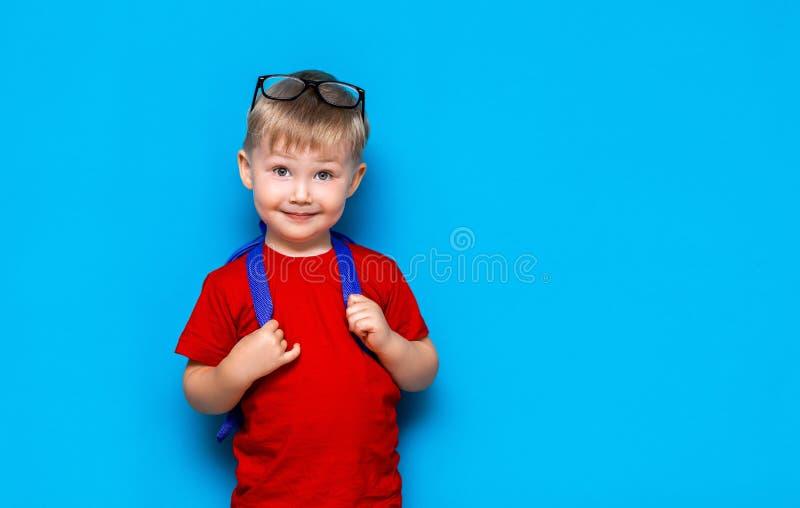 Счастливый усмехаясь мальчик в красной футболке со стеклами на его голове идет обучить в первый раз Ребенок с сумкой школы Ребенк стоковое изображение