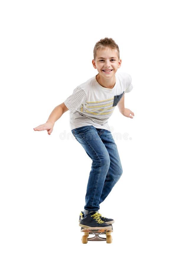 Счастливый усмехаясь мальчик ехать скейтборд стоковые изображения rf