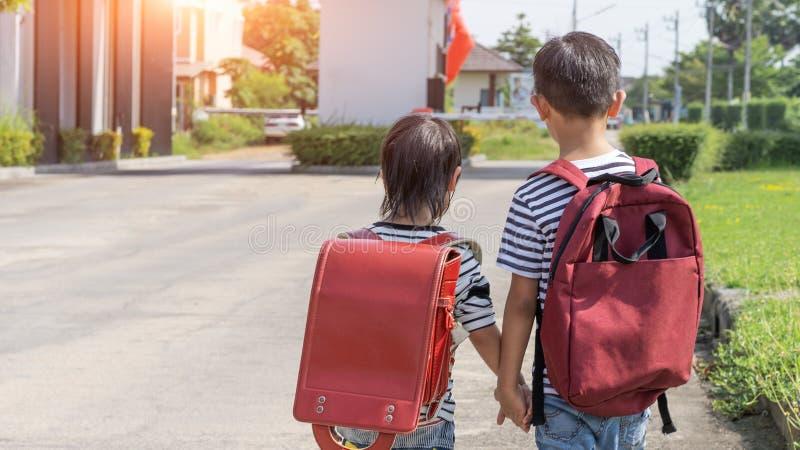 Счастливый усмехаясь ребенк в стеклах идет обучить в первый раз Мальчик ребенка с сумкой идет к начальной школе Ребенок основного стоковое фото