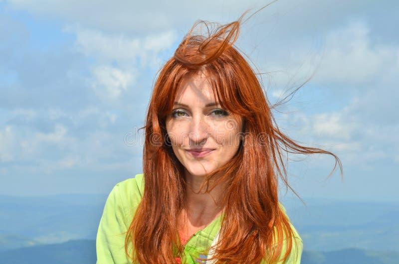 Счастливый усмехаясь турист женщины redhead в солнечном свете в горах против неба, ветер раздражает ее волосы стоковое фото rf