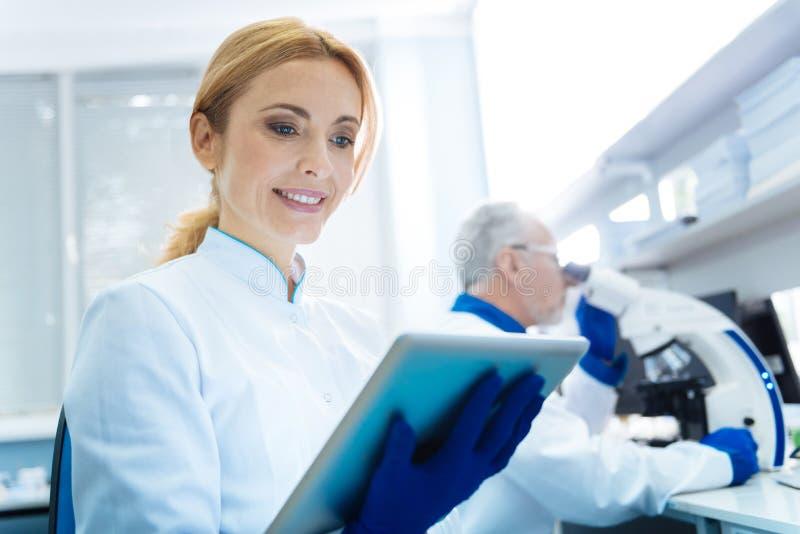 Счастливый усмехаясь ученый женщины в лаборатории стоковые изображения