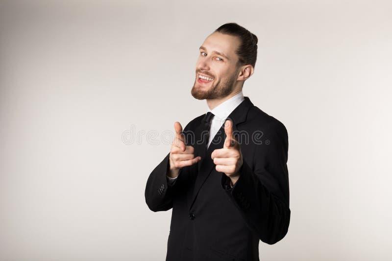 Счастливый усмехаясь человек с бородой и ультрамодным стилем причесок нося черный костюм смотря и указывая на камеру стоковое фото rf