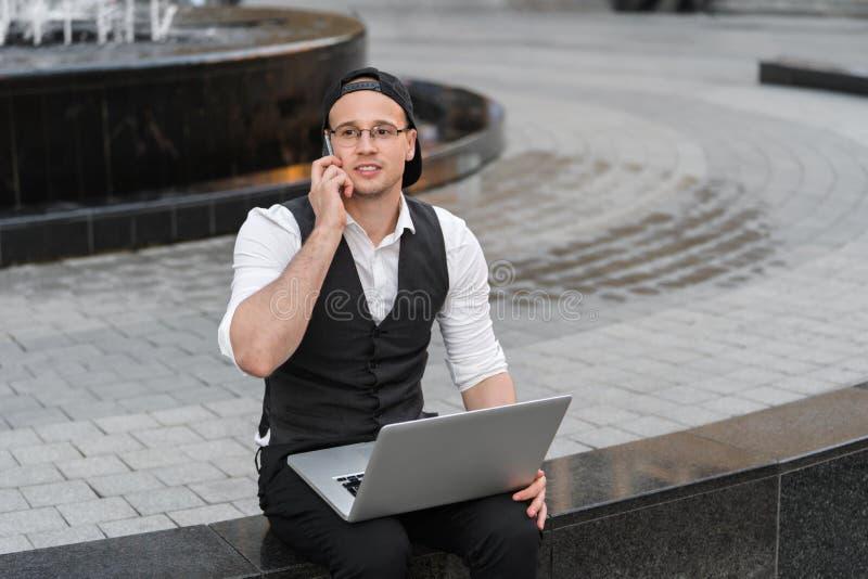 Счастливый успешный фрилансер работая с компьтер-книжкой и телефоном outdoors стоковое изображение rf