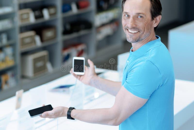 Счастливый человек выбирая один smartphone для себя стоковые изображения