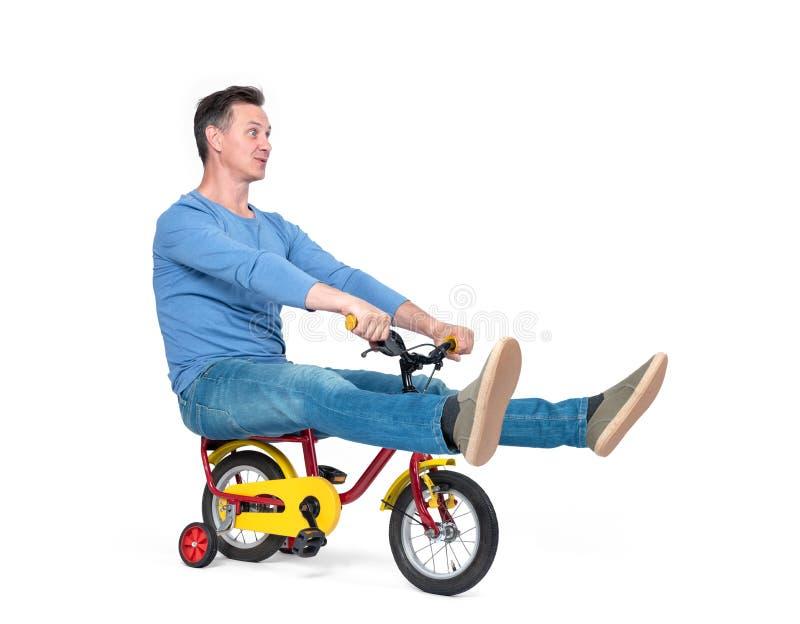 Счастливый человек в джинсах и футболке на велосипеде детей, изолированном на белой предпосылке стоковая фотография