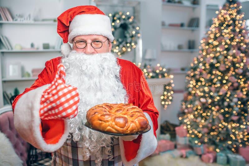 Счастливый человек в одеждах Санта Клауса держит пирог и показывает большой большой палец руки вверх Гай смотрит на камере Он в п стоковые изображения rf