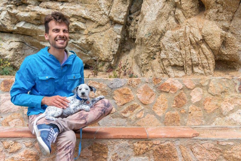 Счастливый человек счастливый держащ его принятого смешанного далматинского щенка и сидящ на каменном стенде Концепция принятия л стоковая фотография
