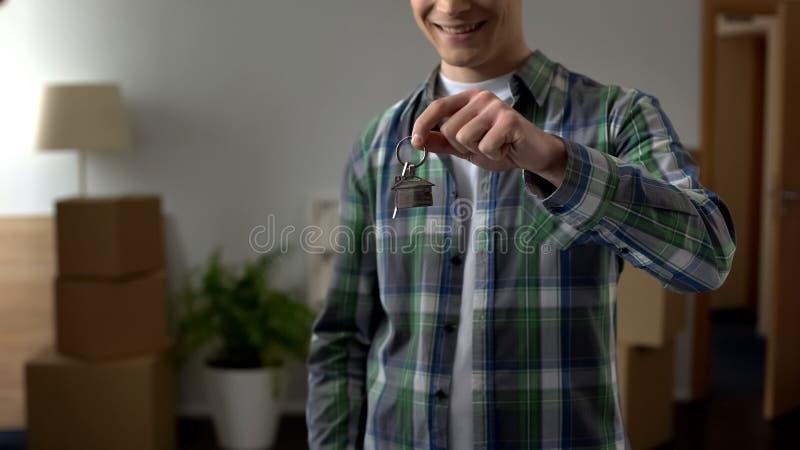 Счастливый человек держа ключи к новой квартире, доступному банковскому кредитованию, ипотеке стоковое фото