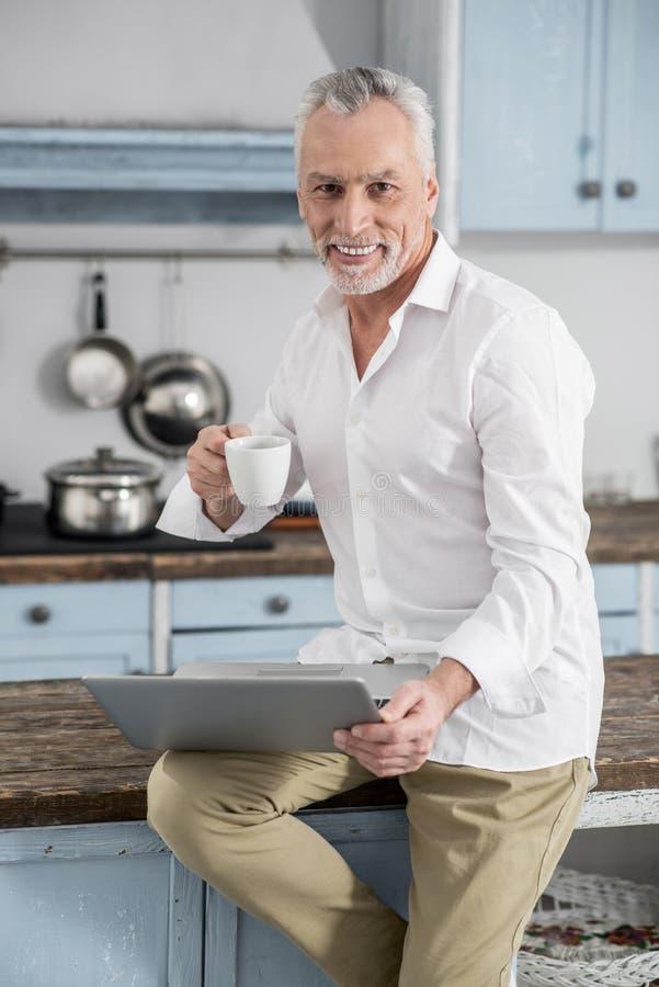 Счастливый человек держа компьтер-книжку на его колене стоковое изображение rf